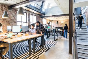Team members huddled over laptops at an industrial-chic startup space