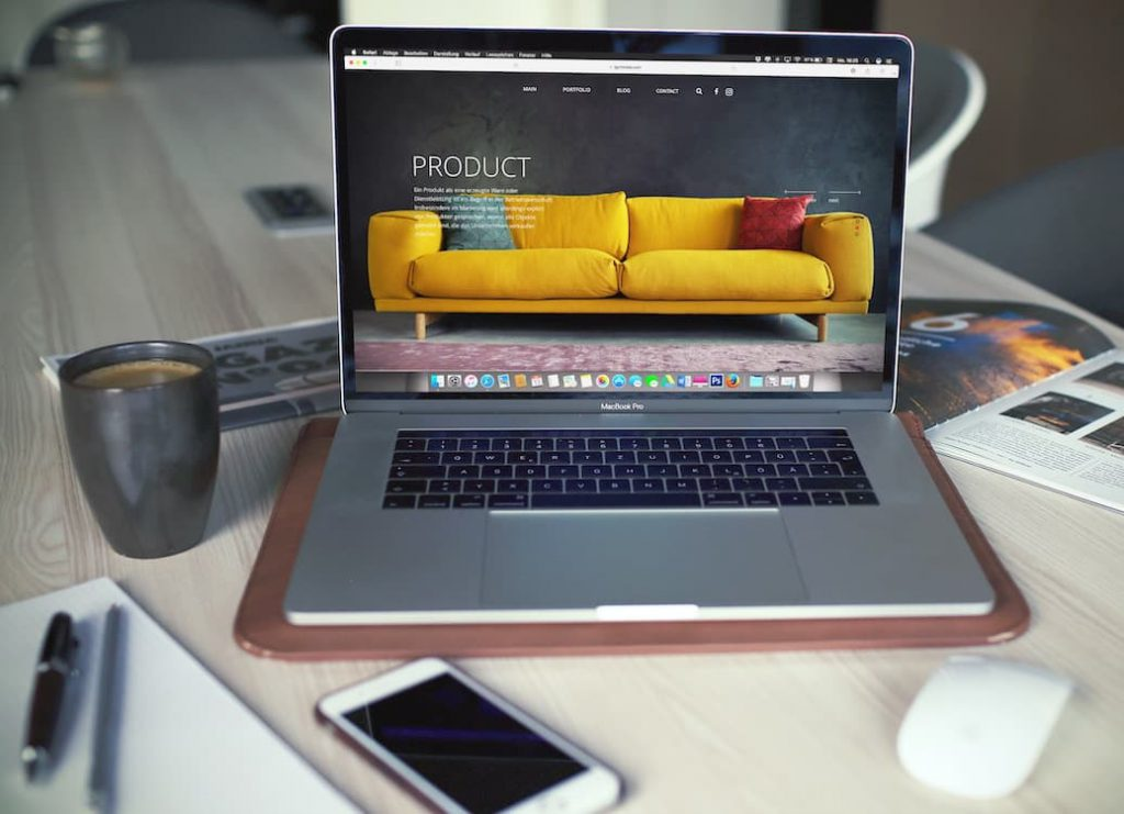 Laptop screen open to a website displaying a yellow sofa and product description