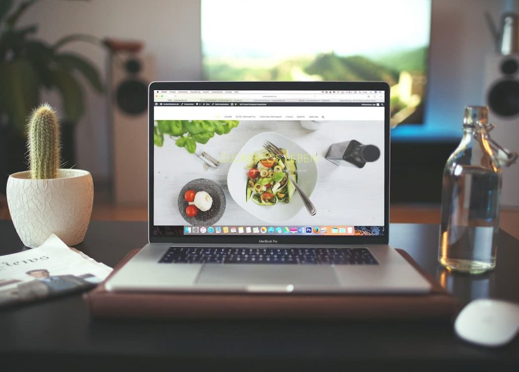 Laptop open to foodie website, displaying image of a bowl of pesto pasta