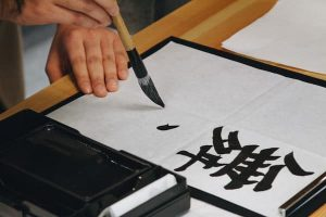 Person painting Chinese calligraphy