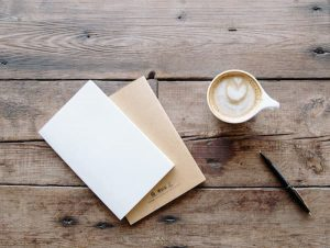 Cappuccino, two notebooks and a pen against a wooden table