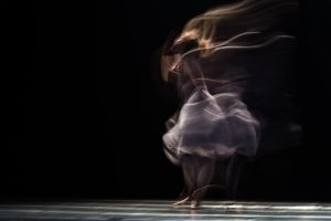 Blurred-motion image of a graceful dancer spinning on stage