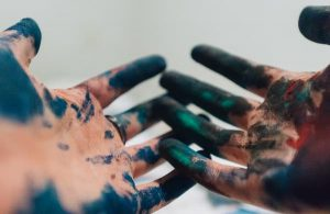 Person's hands covered in paint