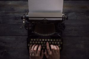 Woman's hands typing on old-fashioned typewriter against wooden table